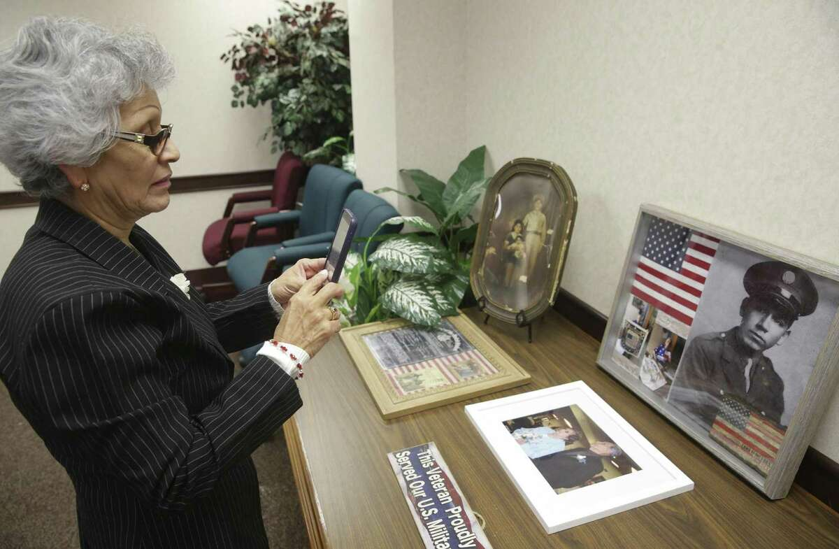 Daughter Margaret Garay takes a photo of of old portraits as U.S. Congressman Joaquin Castro awards five military service medals to the family of Anselmo Castro, a WWII vetaran, on December 21, 2016.