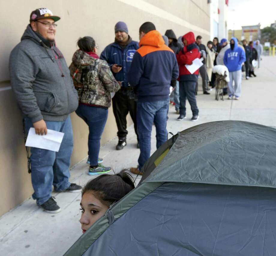Danessa Lopez sticks her head out of her tent Tuesday morning as she waits for Best Buy to open so she can buy a NES Classic game console. Lopez, joined her cousin and uncle on Monday afternoon to wait outside the store to ensure they would be first in line to get one of the game systems. Photo: William Luther, Staff / San Antonio Express-News / © 2016 San Antonio Express-News