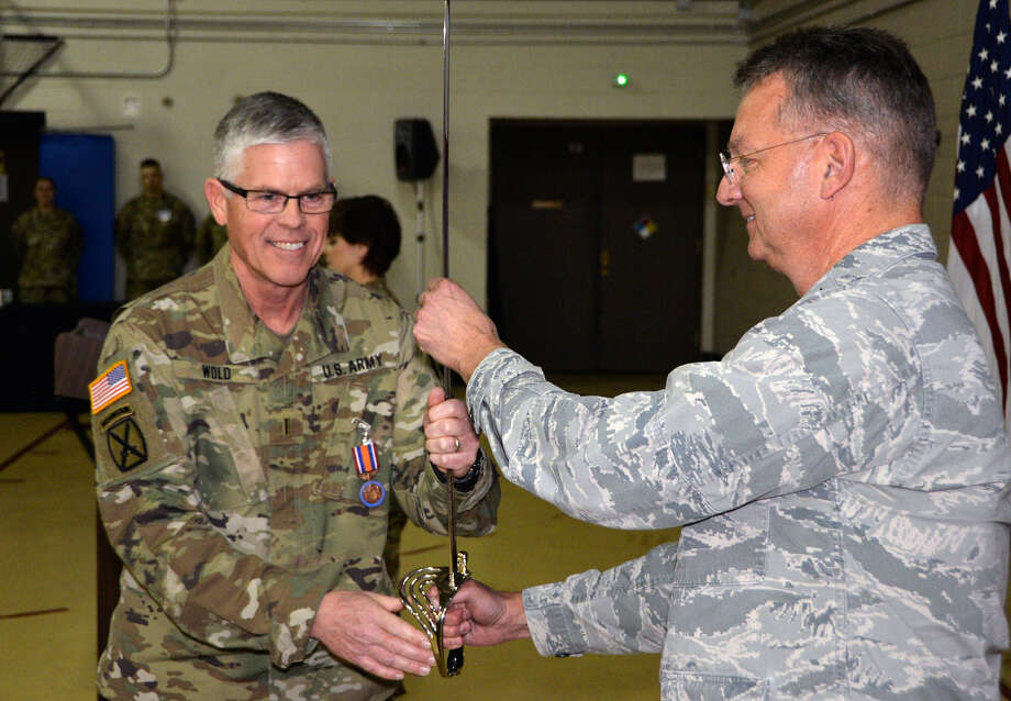 Division of Military and Naval Affairs Chief Warrant Officer Robert Wold passes a ceremonial saber to Maj. Gen. Anthony German during a ceremony in Latham.