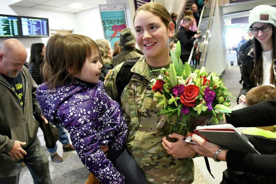 Pvt. Erin Charton of Colonie, center, holds her sister Laura Charton, 3, as her family celebrates her return home on leave from the Army for Christmas on Wednesday, Dec. 21, 2016, at the Albany International Airport in Colonie, N.Y. (Cindy Schultz / Times Union) Photo: Cindy Schultz / Albany Times Union