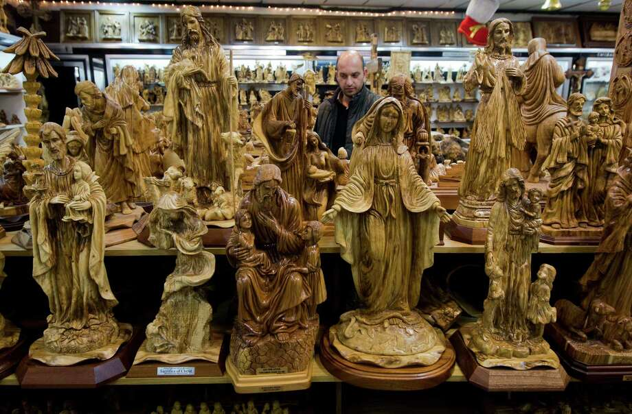 A merchant looks over his wares in a souvenir shop in Bethlehem. Some shops are trying to fight an import trend, stocking their shelves almost exclusively with locally made products.  Photo: Majdi Mohammed, STF / Copyright 2016 The Associated Press. All rights reserved.