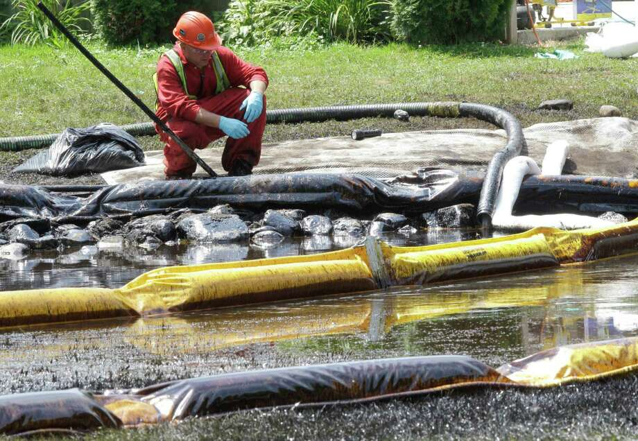 A worker monitors water in Michigan's Talmadge Creek as booms trap oil from a ruptured pipeline. The crafting of new safety measures began after the 2010 break, which sent crude into the Kalamazoo River. The suit filed Thursday, Oct. 8, 2015 by the National Wildlife Federation says the federal Oil Pollution Act prohibits operators from handling, storing or transporting oil until their spill response plans get federal approval. The plans are supposed to make sure enough resources are available to contain and remove spilled oil and limit environmental damage. (AP Photo/Paul Sancya, File) Photo: Paul Sancya, STF / AP