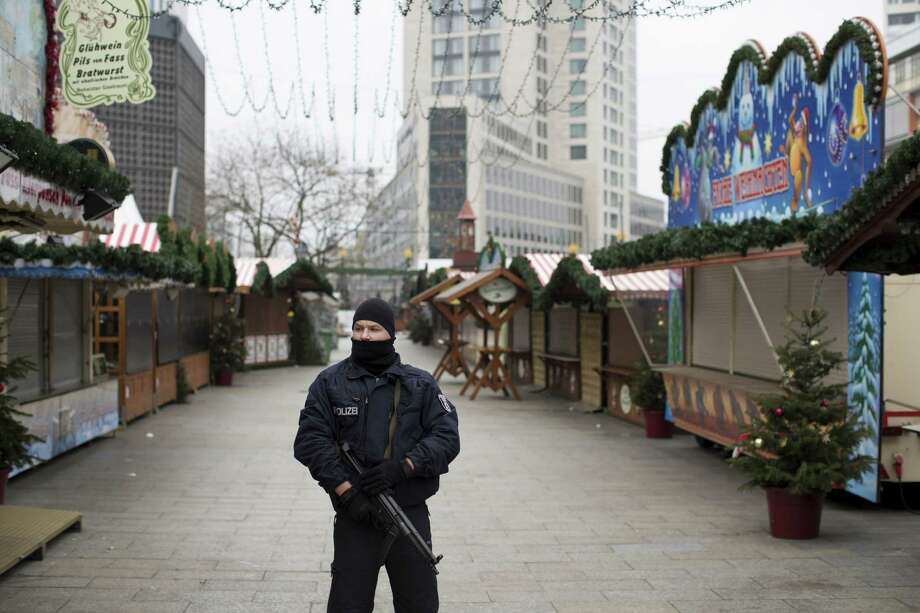 An armed police officer stands guard Wednesday at the Berlin Christmas market. Investigators intensified their search for a Tunisian national linked to Monday's deadly truck assault. Photo: Jasper Juinen / © 2016 Bloomberg Finance LP