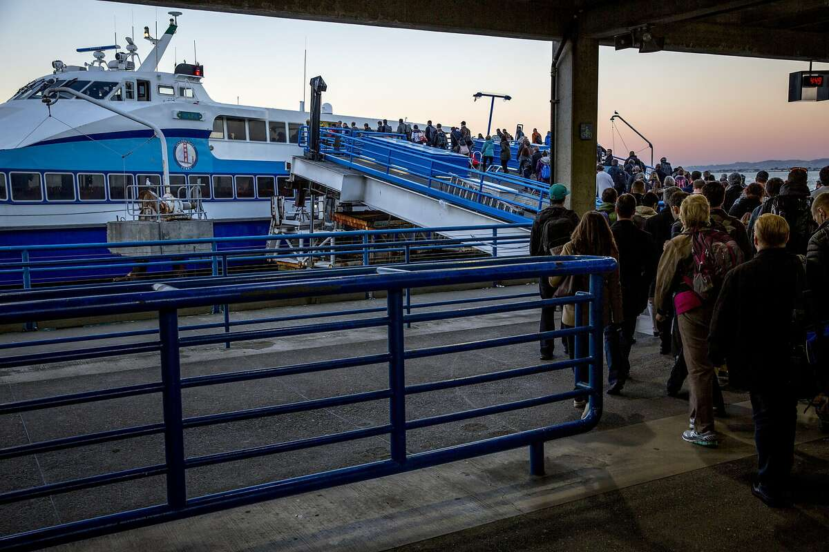FILE-- People board to ride the 5 p.m. ferry heading to Larkspur at the Golden Gate San Francisco Ferry Terminal behind the Ferry Building on Wednesday, Dec. 21, 2016 in San Francisco.City, port and ferryboat officials broke ground Thursday on a $79 million project to build two San Francisco ferry docks that mark a major expansion of water transportation.