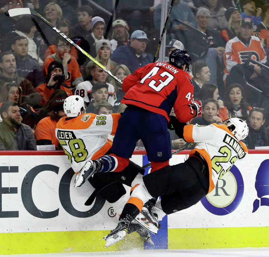 Philadelphia Flyers' Taylor Leier (58) and Brandon Manning (23) collide with Washington Capitals' Tom Wilson (43) during the second period of an NHL hockey game, Wednesday, Dec. 21, 2016, in Philadelphia. (AP Photo/Matt Slocum) ORG XMIT: PXC109 Photo: Matt Slocum / Copyright 2016 The Associated Press. All rights reserved.