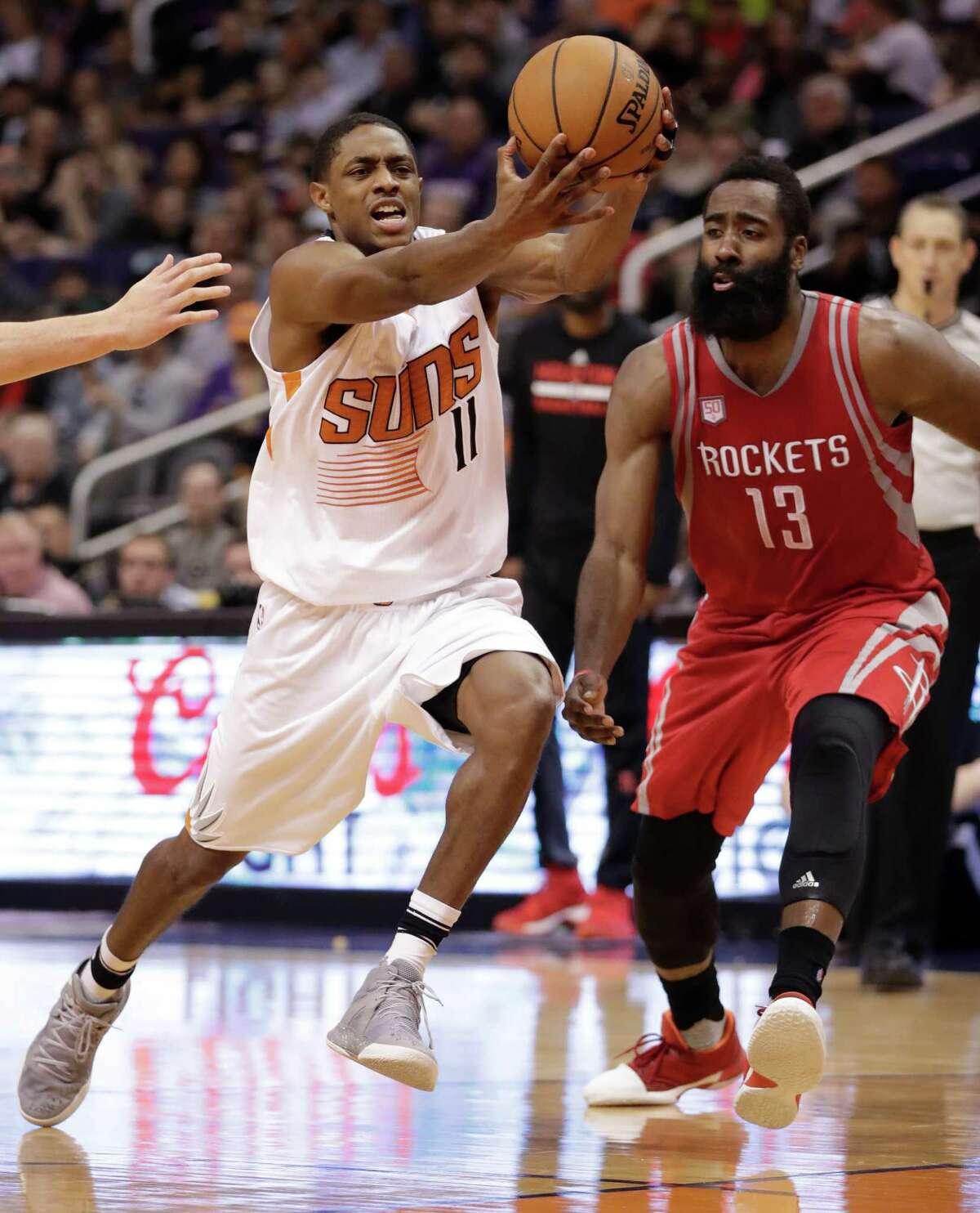 Phoenix Suns guard Brandon Knight (11) drives past Houston Rockets guard James Harden (13) during the second half of an NBA basketball game, Wednesday, Dec. 21, 2016, in Phoenix. (AP Photo/Matt York)