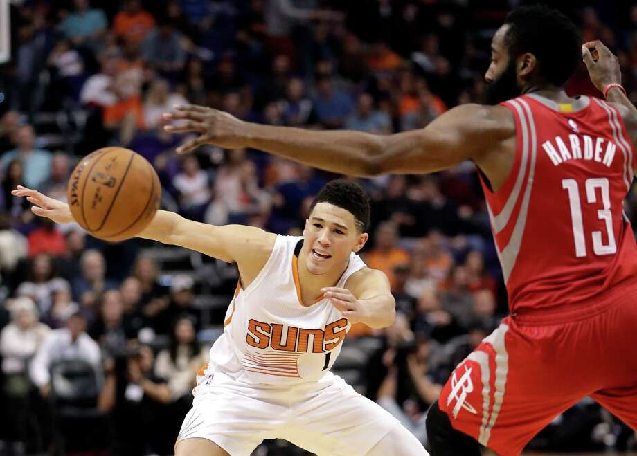 Phoenix Suns guard Devin Booker (1) loses the ball as Houston Rockets guard James Harden (13) defends during the second half of an NBA basketball game, Wednesday, Dec. 21, 2016, in Phoenix. (AP Photo/Matt York) Photo: Matt York, Associated Press / Copyright 2016 The Associated Press. All rights reserved.