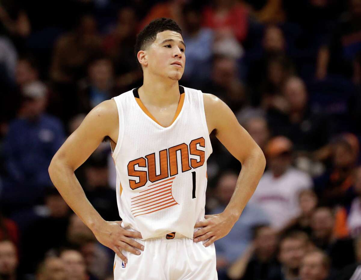 Phoenix Suns guard Devin Booker pauses during a stop in play in the second half of the team's NBA basketball game against the Houston Rockets, Wednesday, Dec. 21, 2016, in Phoenix. (AP Photo/Matt York)