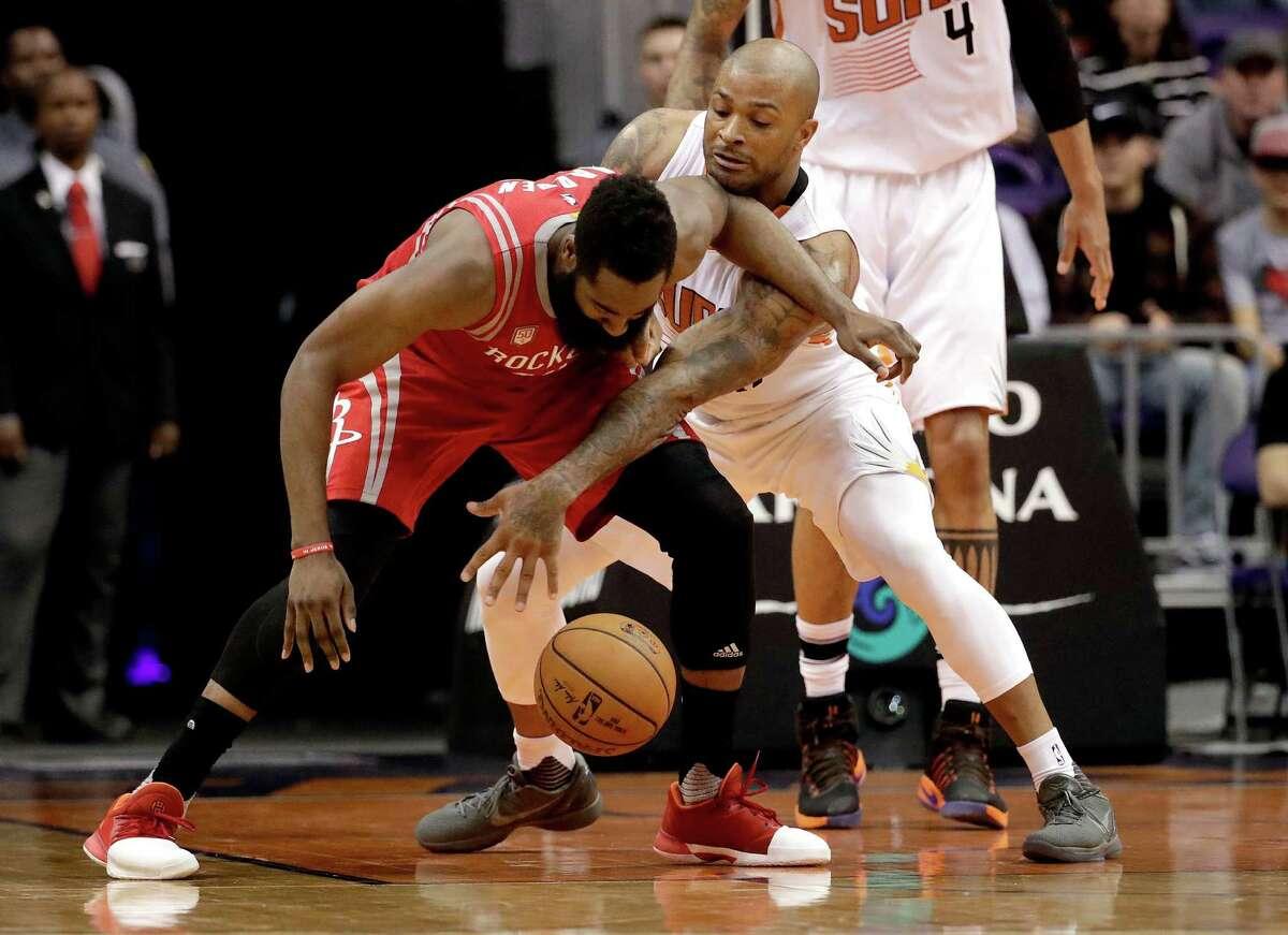 Houston Rockets guard James Harden, left, and Phoenix Suns forward P.J. Tucker battle for the ball during the second half of an NBA basketball game, Wednesday, Dec. 21, 2016, in Phoenix. (AP Photo/Matt York)