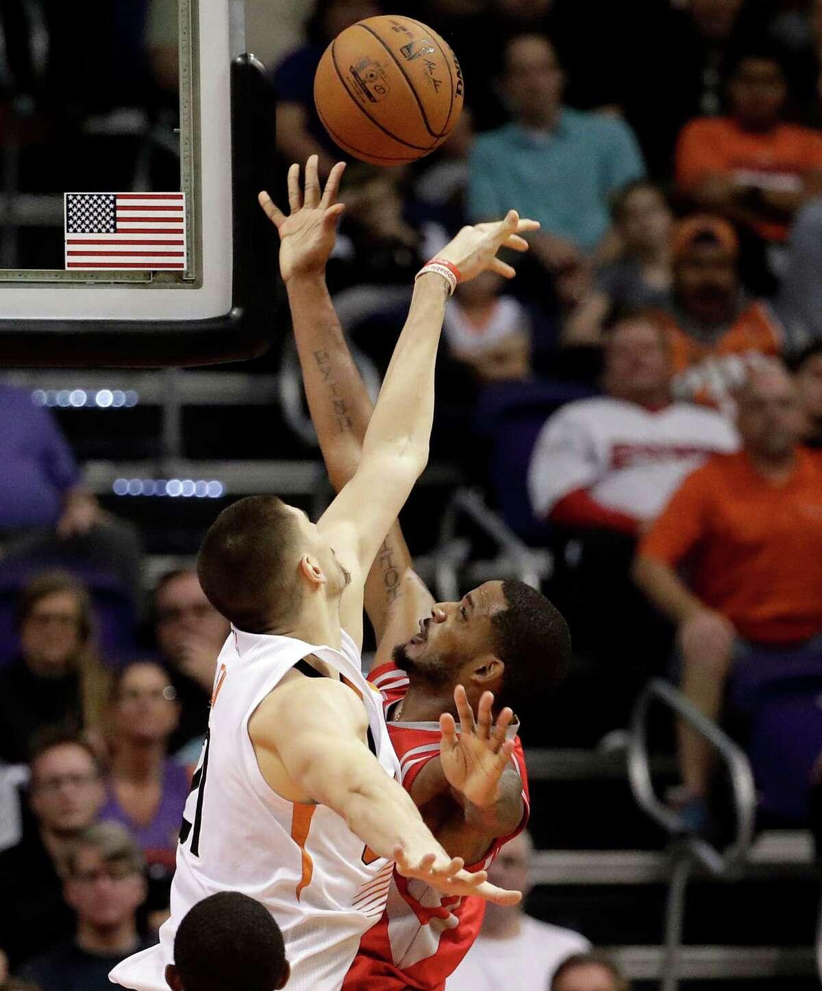 Phoenix Suns center Alex Len, left, blocks the shot of Houston Rockets guard Eric Gordon during the second half of an NBA basketball game, Wednesday, Dec. 21, 2016, in Phoenix. (AP Photo/Matt York)