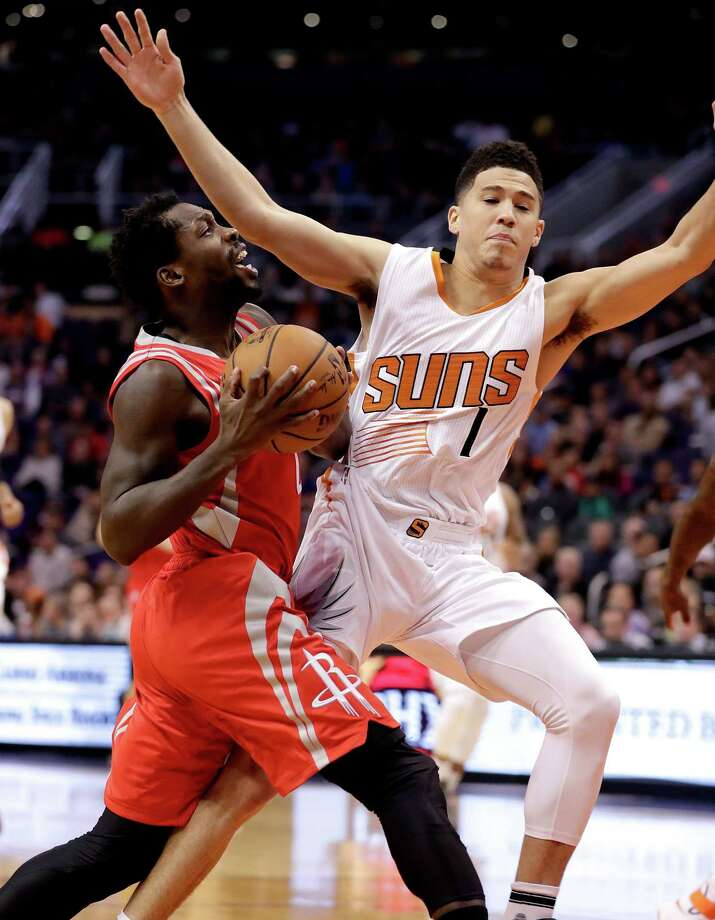 Rockets guard Pat Beverley finds his way to the basket blocked by the wingspan of Suns guard Devin Booker, right, during the first half Wednesday night. Photo: Matt York, STF / Copyright 2016 The Associated Press. All rights reserved.