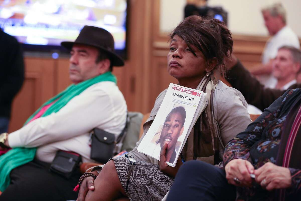 """Paulette Brown holds a sign reading """"Crime Bulletin"""" with the face of her son on it at City Hall in San Francisco as the police commission votes on the long-awaited use-of-force policy on Wednesday, December 21, 2016. Brown lost her son her 17-year-old son Aubrey Abrakasa to gun violence nine years ago."""