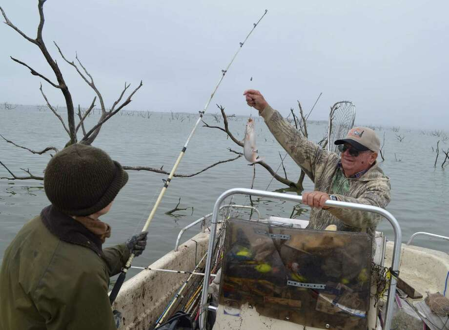 Swinging a chunky blue catfish into the hands of veteran guide Charlie Brown during a cold December morning trip to Choke Canyon Reservoir, Dr. Catherine Cook of San Antonio gets into the holiday spirit — catfish style — that takes over the lake this time of year. Photo: Ralph Winingham /For The Express-News