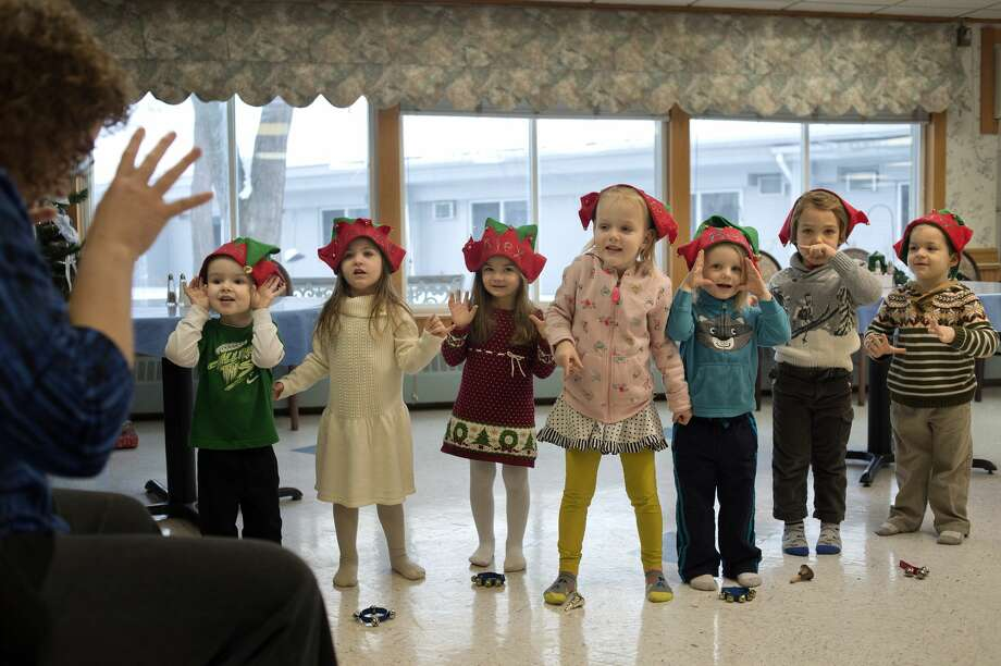 """Stormi's Montessori teacher Tanya Searle, left, leads preschoolers from left: Ethan Sutherland, Charlotte Acosta, Alex Sovis, Marielle Pfeiffer, Beau Broker, Eli Jones and Drew Sovis in a Christmas song at Brittany Manor Wednesday morning. The preschoolers sang a few songs for residents and handed out cards they made at school. """"We wanted to do a service project with the children so that they understand about helping others,"""" Stormi Sutherland, founder of Stormi's Montessori, said. """"It's important for children to give back to their community."""" Photo: Brittney Lohmiller/Midland Daily News"""