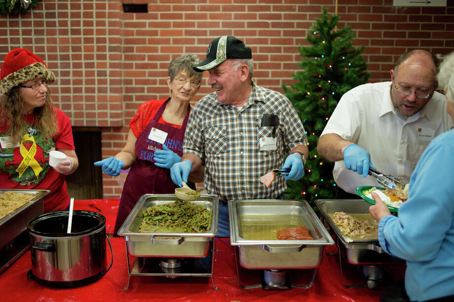 BRITTNEY LOHMILLER | blohmiller@mdn.net St. John's Lutheran Church members from left: Judy Ruttan, Elmer Thurston and Bruce Siebert dish out servings of gravy, green beans and turkey during St. John's Lutheran Church's annual Christmas dinner in 2015.