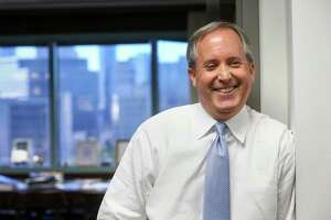 Texas Attorney General Ken Paxton jokes with staff members at his office Friday, Oct. 21, 2016, in Austin.