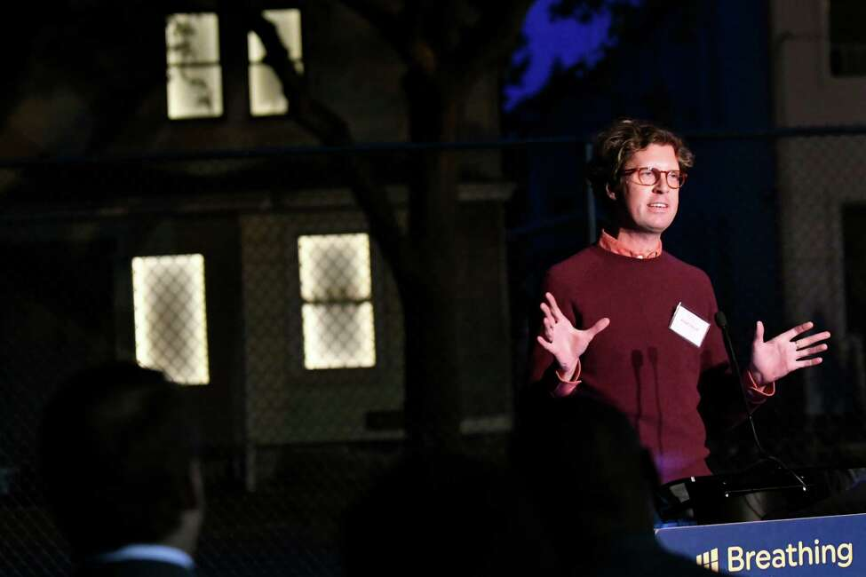 Artist Adam Frelin speaks during a news conference to launch the Breathing Lights project on Thursday, Sept. 29, 2016, in Schenectady, N.Y. Behind him, an abandoned house on Stanley Street pulses with light. (Cindy Schultz / Times Union)