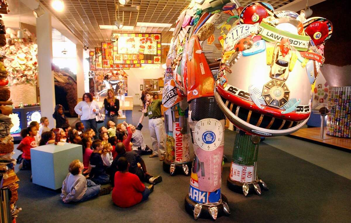 Second-graders from Woodward School in Stratford try to locate items on the Trash-O-Saurus, a sculpture in The Garbage Museum made entirely from items that had been thrown out. The sculpture weighed one ton, and represented the amount of garbage produced by one person in one year.
