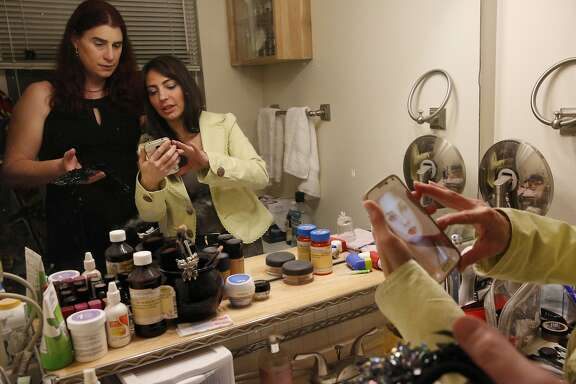 Billie Lynn, left, looks at a reference photograph pulled up by her longtime family friend Serenity Polizzi for Polizzi to use while doing Lynn's makeup as Lynn and her partner get ready in Lynn's home for her company SAP's formal themed holiday party Dec. 17, 2016 in San Jose, Calif.