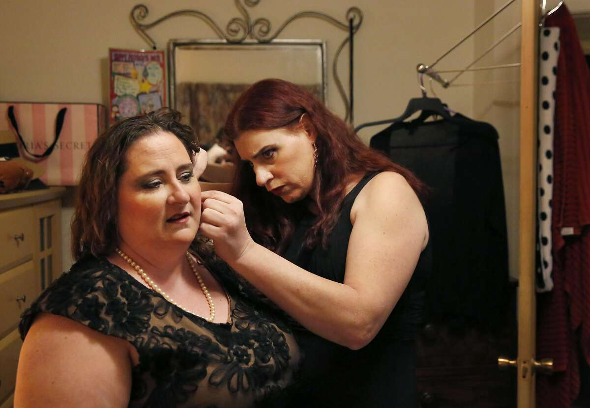 Billie Lynn helps her partner Maggie Anderson put in earrings as they get ready in Lynn's home for her company SAP's formal themed holiday party Dec. 17, 2016 in San Jose, Calif.