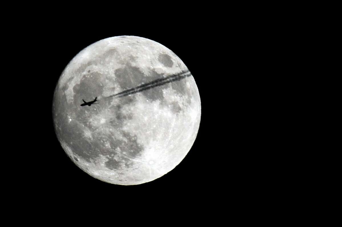 An airplane flies past the moon above Stamford, Conn. on Sunday, Nov. 13, 2016. This supermoon is the closest the moon has been to Earth since 1948 and will not be as close again until 2034.