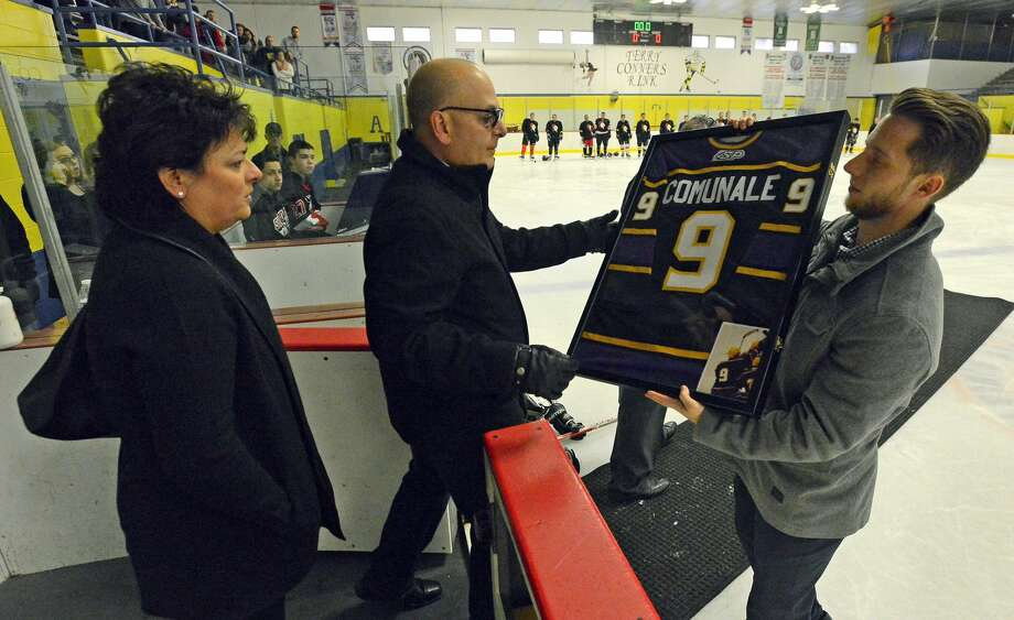 FILE — John Mixus, a childhood friend and former Westhill High hockey alumnus, presents the parents of Joey Comunale, Pat and Lisa Comunale,  Joey's jersey from Westhill High School, after his number 9 was retired in a ceremony prior to the annual alumni ice hockey game at Terry Conners Rink in Stamford on Saturday, Nov. 26, 2016. Over 500 people representing family, friends and hockey alumni attended the ceremony and game. Comunale, who was found murdered on Nov. 13, 2016,  was laid to rest on Tuesday. Photo: Matthew Brown/Hearst Connecticut Media