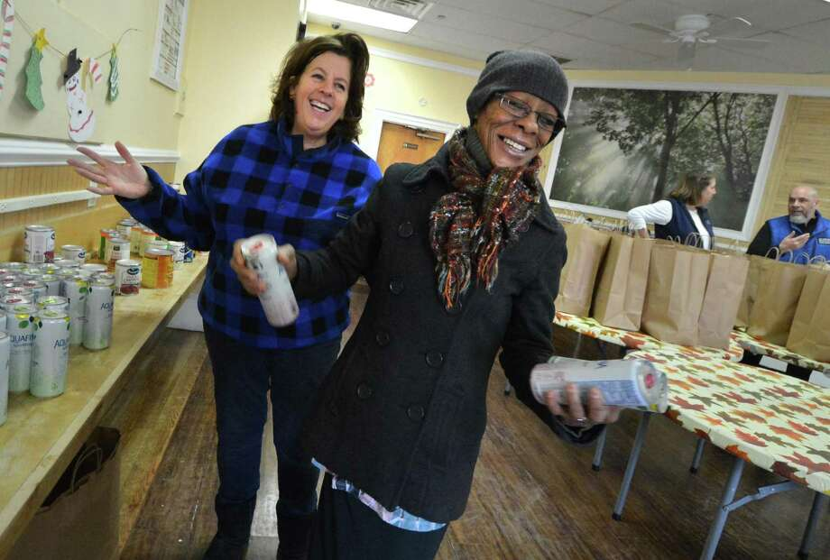 Volunteer Carol Cheswick from the First Congregational Church of Darien helps Chyretta Robinson fill her bag with some drinks to make a complete Christmas dinner from the the Open Door Shelter in Norwalk. More than 125 families will benefit from the program. Photo: Alex Von Kleydorff / Hearst Connecticut Media / Connecticut Post