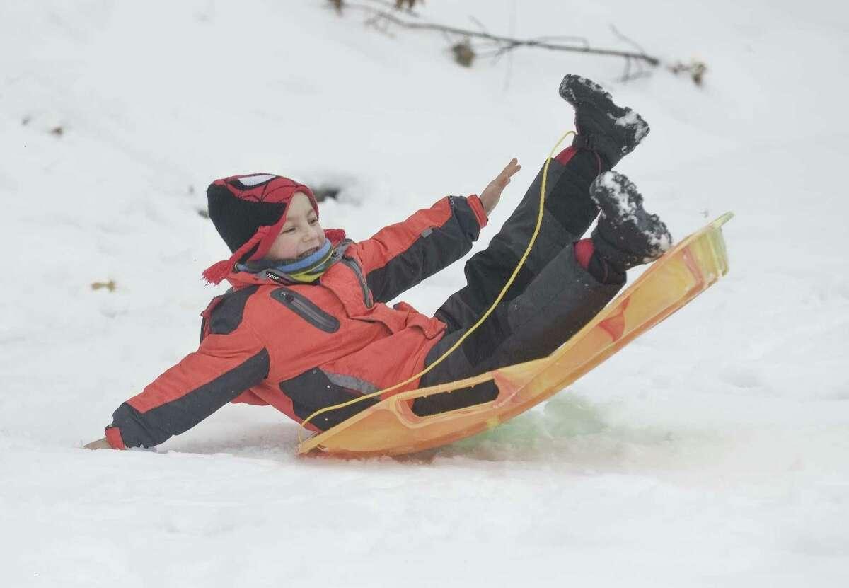 Alex Nikolas, 6 of Darien, sleds down a small hill at Brien McMahon High School on Saturday.