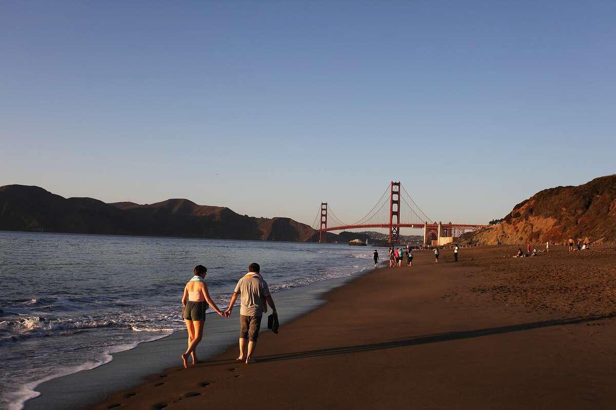 Kelly Martin and Robert Da Silva (l-r) walk on Baker Beach just before sunset on October 5, 2013 in San Francisco, Calif.