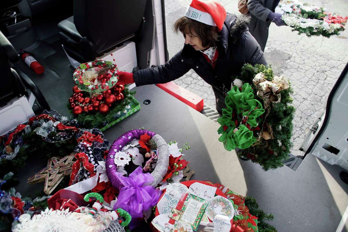 Nancy DeCesare, a medical records specialist, unloads some of the Times Union Circles of Caring Contest wreaths at the Visiting Nursing Association on Thursday, Dec. 15, 2016, in Albany, N.Y. (Paul Buckowski / Times Union)