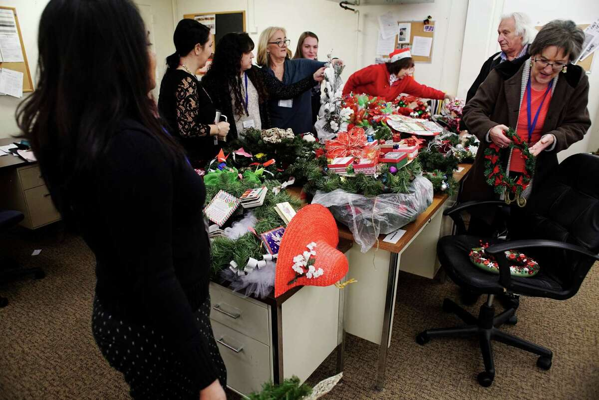 Visiting Nursing Association employees, from left to right, Roxanne Ramlall, Tami Fontaine, Michelle Powers, Fran Schumacher, Kira Millard, Nancy DeCesare, Frank DiPietro and Rachel Swire, look over all of the Times Union Circles of Caring Contest wreaths on Thursday, Dec. 15, 2016, in Albany, N.Y. (Paul Buckowski / Times Union)