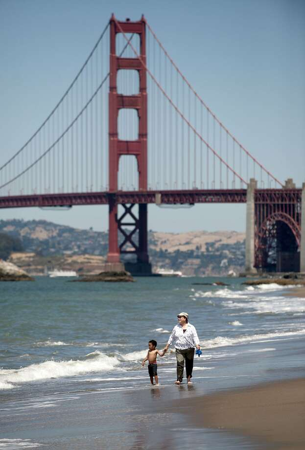 People walk on Baker Beach in San Francisco, Calif., on July 28, 2010. On Thursday afternoon, a woman drowned in the waters off the beach in the Presidio, officials said. Photo: Chad Ziemendorf, The Chronicle