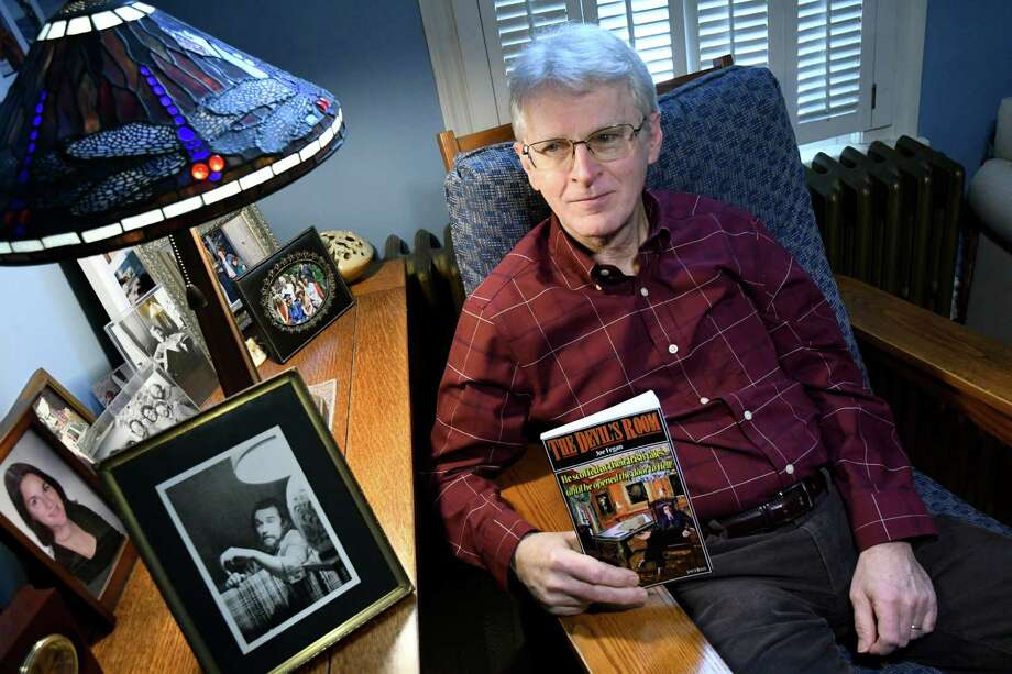 """Author Jeff Durstewitz holds """"The Devil's Room,"""" which he wrote under the pen name of  Joe Fegan, on Wednesday, Dec. 21, 2016, at his home in Saratoga Springs, N.Y. His friend Campbell Black, pictured in the circa 1975 photograph at left, was the inspiration for the main character. (Cindy Schultz / Times Union) Photo: Cindy Schultz / Albany Times Union"""