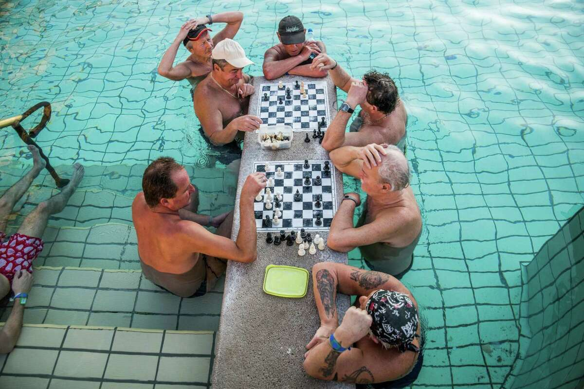 FILE - In this March 21, 2016 file photo visitors play chess in a pool of Szechenyi Thermal Bath and Swimming Pool in Budapest, Hungary. The city of Budapest has centuries of experience with the art of relaxation, thanks to its public baths, where you can sink neck-deep in hot mineral waters. (Zoltan Balogh/MTI via AP, file) ORG XMIT: XMTI208