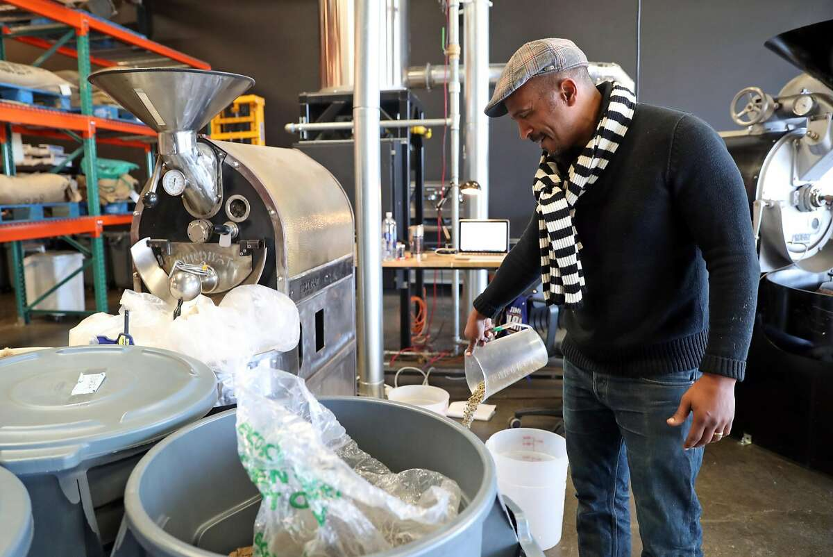 Keba Konte pours Tanzanian coffee beans into a container at Red Bay Coffee in Oakland, Calif., on Thursday, December 22, 2016.