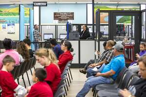 Daniel Solis (top left) takes his picture taken by Kim Tompkins for Solis' new driver's license at the Department of Motor Vehicles on Thursday, Dec. 22, 2016 in Hayward, Calif. Solis, originally from Mexico now living in Hayward for the past six years, recently attained permanent resident status and renewed his AB 60 driver's license to a regular license. More than 800,000 people have received California drivers licenses in the past two years under a 2-year-old law that allows people living in the country without documentation to legally drive in the state. Solis previously applied for the AB 60 license within a couple months after the law passed.