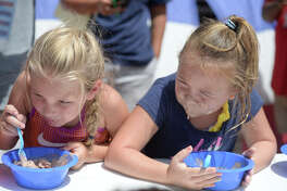 Krista Law, age 5, and Abigail Lindsey, age 6, compete in an ice cream eating contest during an Ice Cream Festival hosted by Do 432 featuring inflatable water slides from Tiki Island Waterpark, Saturday, July 30, 2016, in a parking lot near S. Big Spring Street and W. Kentucky Ave. James Durbin/Reporter-Telegram