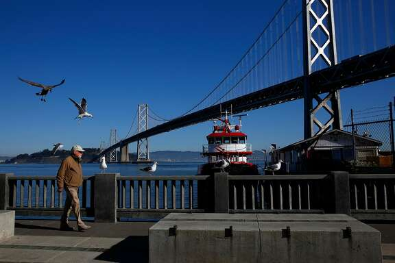 A pedestrian walks past the new St. Francis fireboat docked at Fire Station 35 at Pier 22 1/2 Dec. 22, 2016 in San Francisco, Calif.