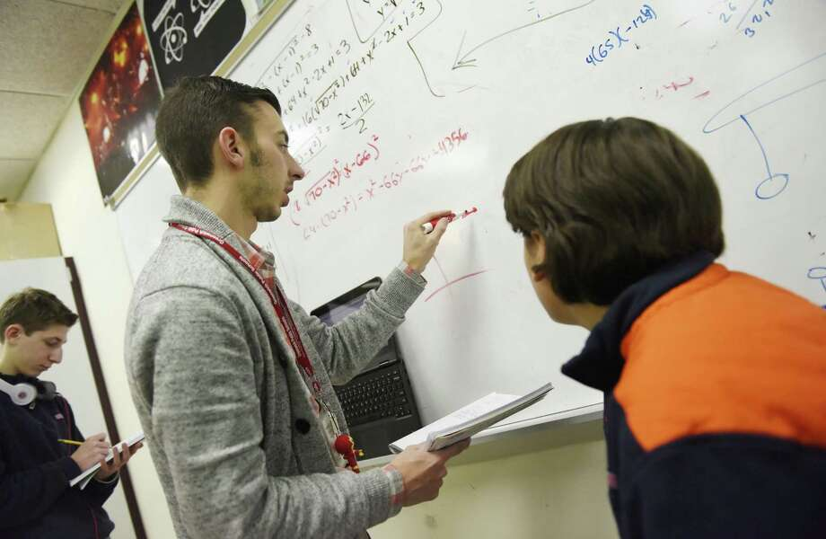 Brian Walach helps students with equations in the Innovation Lab at Greenwich High School in Greenwich, Conn., in December 2015. Bolstered by research, patents, productivity and education, Connecticut scored well on the 2016 installment of the Bloomberg's U.S. State Innovation Index, though slipping two slots to rank seventh nationally. Photo: Tyler Sizemore / Hearst Connecticut Media / Greenwich Time