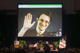 FILE - In this Feb. 14, 2015 file photo, Edward Snowden appears on a live video feed broadcast from Moscow at an event sponsored by ACLU Hawaii in Honolulu. A declassified report on a congressional investigation into Edward Snowden says the former National Security Agency contractor has remained in contact with Russian intelligence services since he arrived in Moscow three years ago. The House Intelligence committee released the report Thursday.   (AP Photo/Marco Garcia, File)