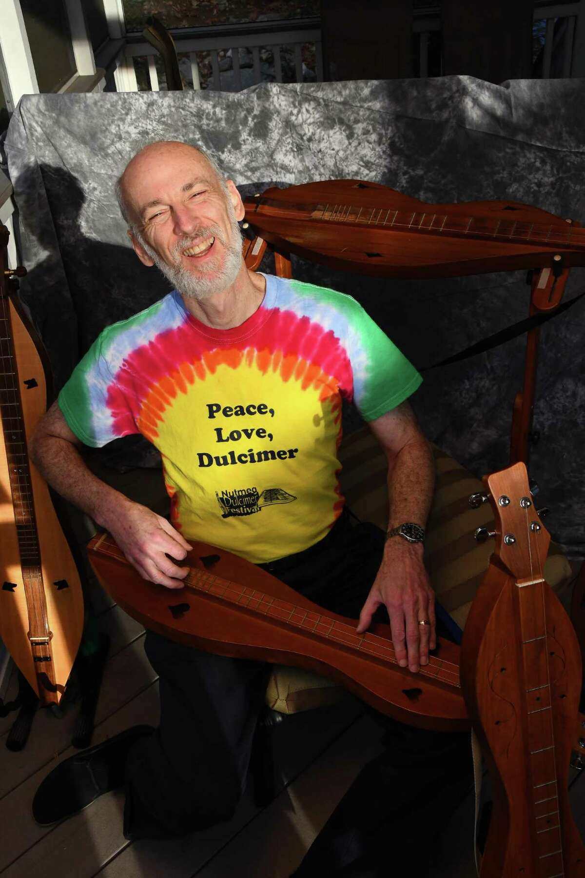 Wearing one of his favorite shirts, Sam Edelston sings and plays one of his many dulcimers.