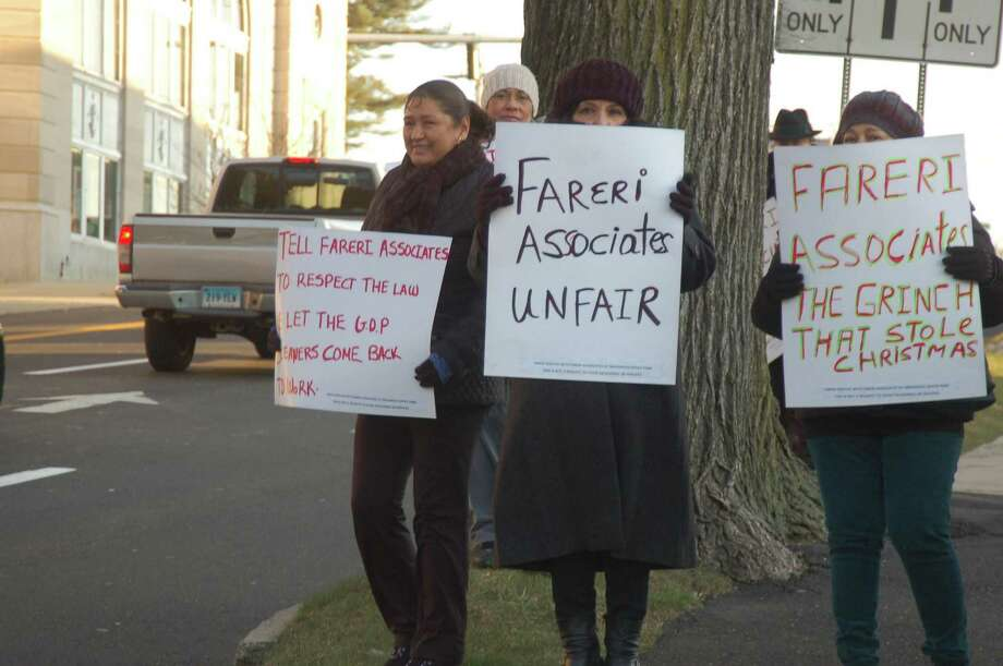 Elidel Garfias, left, Rosalia Bravo and Sonia Osorio, office cleaners at Greenwich Office Park who were fired after Greenwich-based Fareri Associates took over the property last month, protest Thursday outside the company's office on Dearfield Drive. Photo: Ken Borsuk