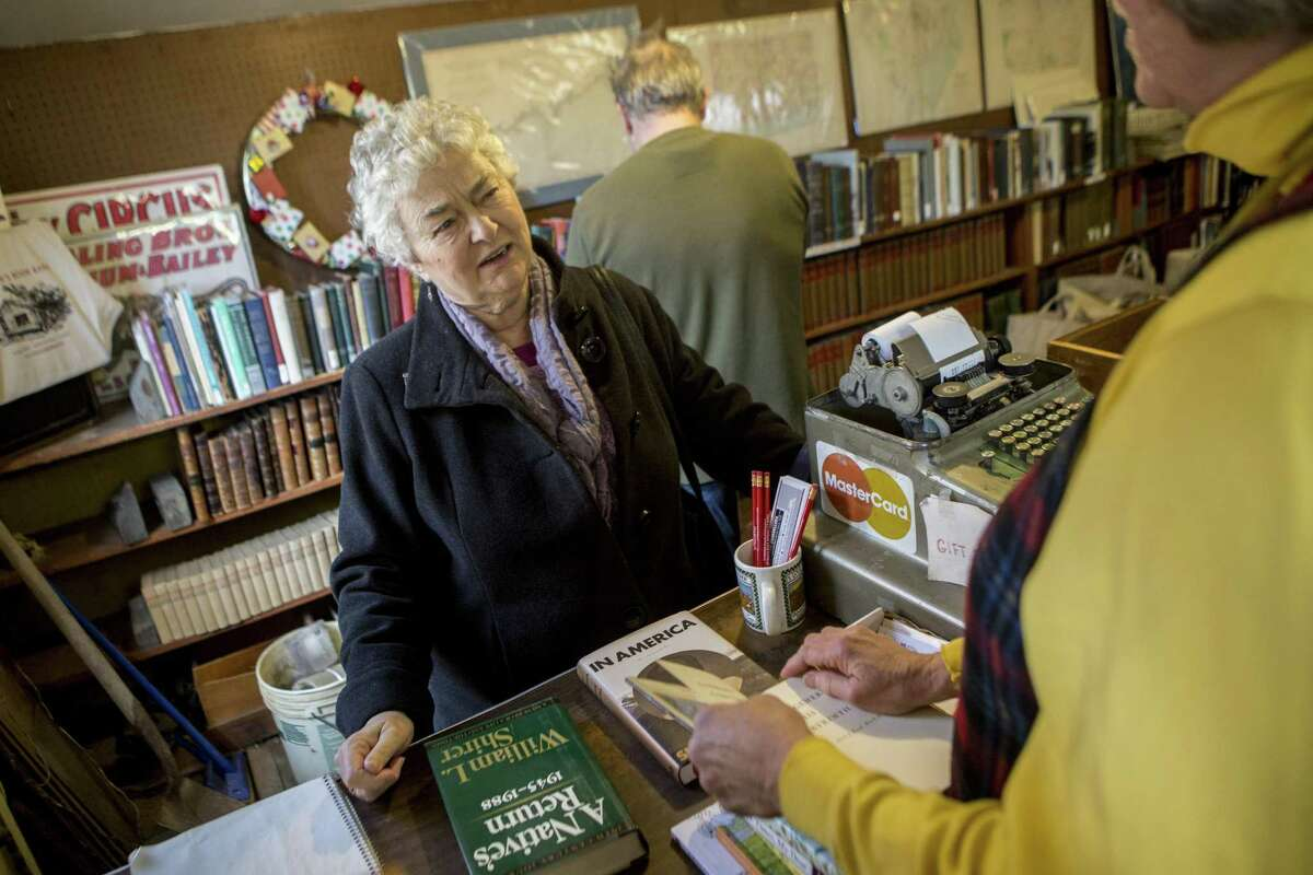 Theresa Childs, left, a regular customer and a Hamden resident, asks Meg Turner, manager of Whitlock's Book Barn in Bethany, if she'd reconsider buying all the books Childs is selling.