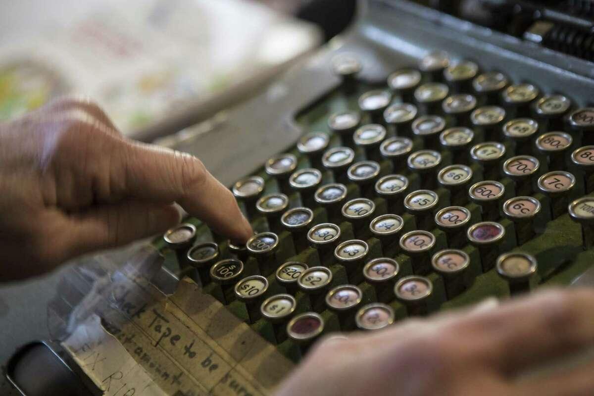 Meg Turner uses a vintage cash register at Whitlock's Book Barn in Bethany.