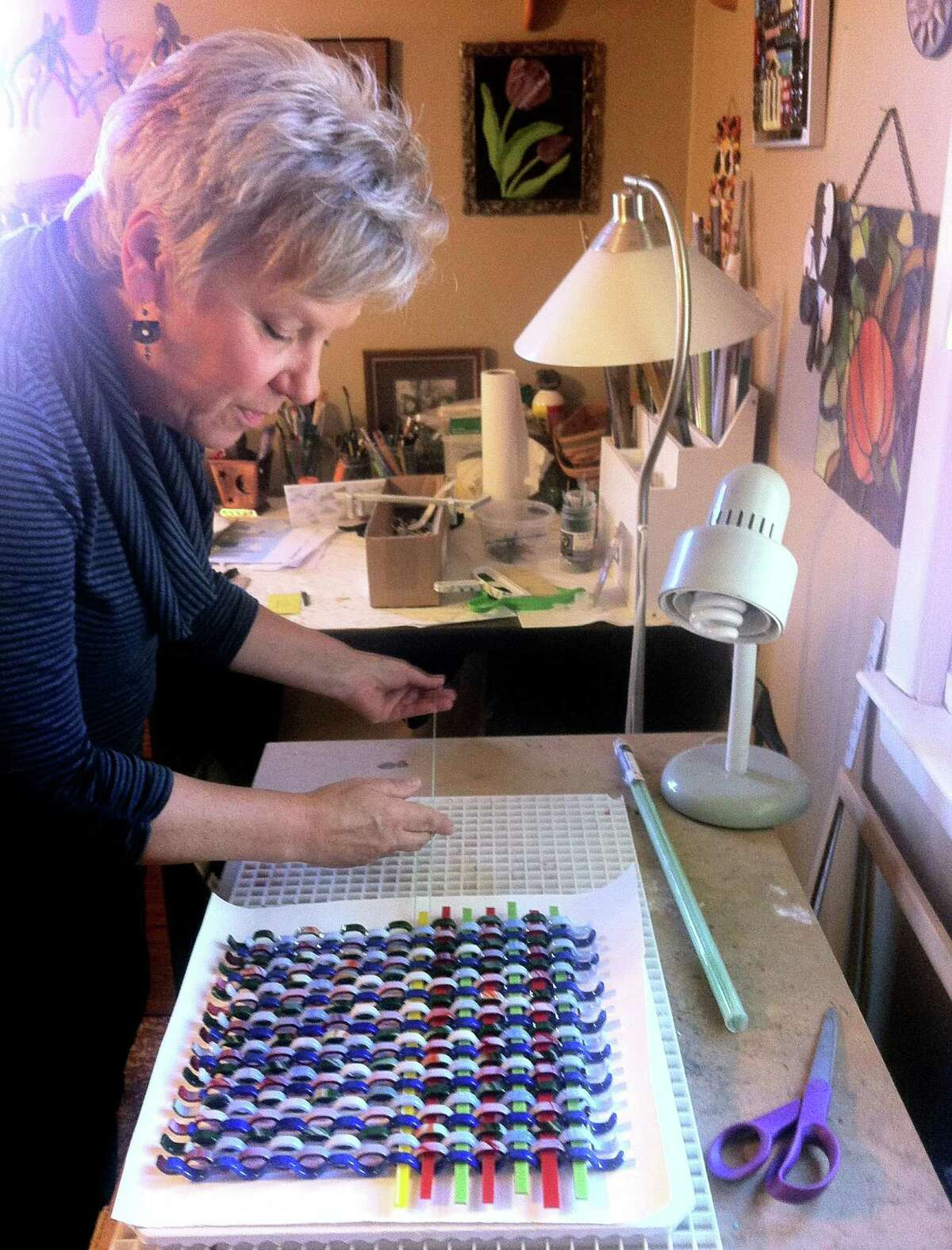 Heidrun Morgan, a glass artist from Newtown, works on one of her woven pieces at her home studio on a recent morning.