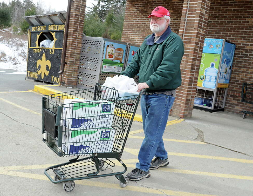 Mike McGuire of Hoosick Falls leaves a Tops grocery store with free water in his cart last February in Hoosick Falls, N.Y. McGuire has been a resident of Hoosick Falls for 63 years and worked at Saint-Gobain for 41 years. (Lori Van Buren / Times Union)