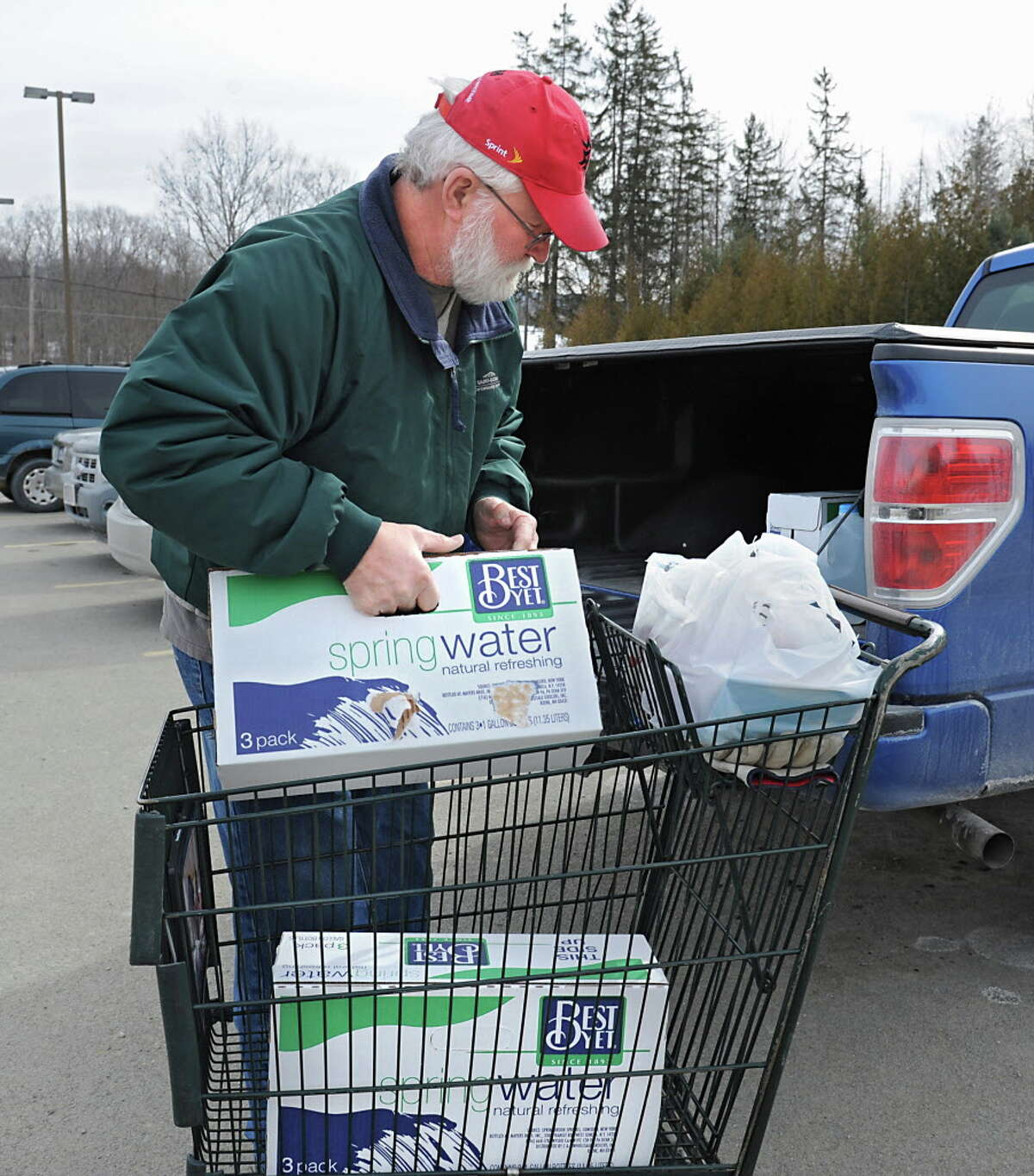 Mike McGuire of Hoosick Falls loads spring water, bought at Tops grocery store, into the back of his pickup truck on Friday, Feb. 12, 2016 in Hoosick Falls, N.Y. (Lori Van Buren / Times Union)