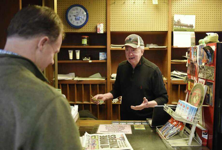 Plaza News owner and sole employee Jimmy Sheerin helps a customer at his newsstand at the Greenwich train station in Greenwich, Conn. Thursday, Dec. 22, 2016. For the past 47 years, Sheerin worked at the newsstand without missing a single day. On Friday, Dec. 30, Sheerin will close up shop due to declining sales at the stand. Photo: Tyler Sizemore / Hearst Connecticut Media / Greenwich Time