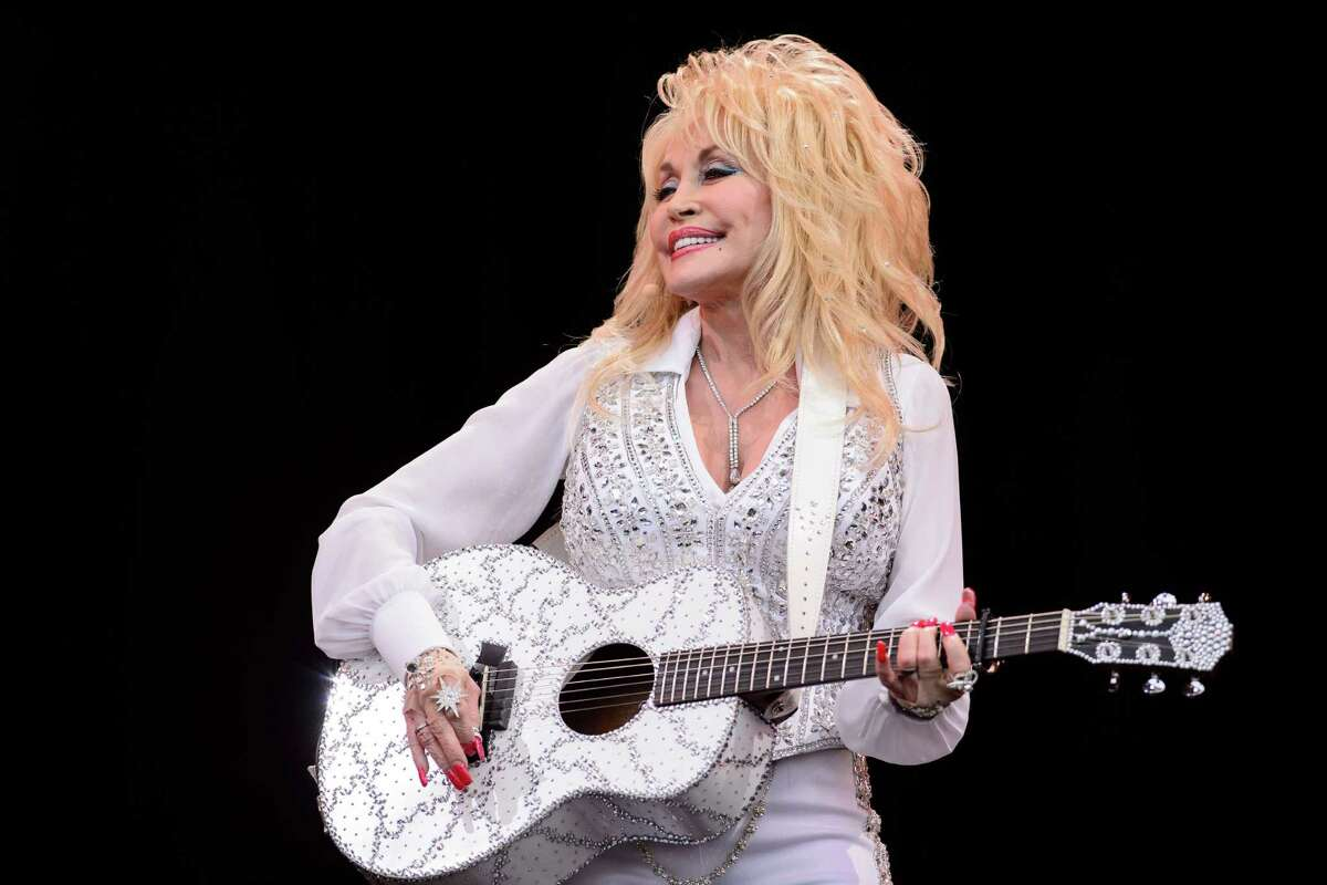 """Dolly Parton (shown performing two years ago) made a grand entrance at the Tobin Center for the Performing Arts to the refrain of Louis Armstrong's signature hit and delivered a show that out-dazzled her glitzy dresses, rhinestone guitars, high heels and big hair. The country music icon headlined the third annual benefit concert for the Tobin Center's Generation NEXT Education Initiative, a gig which has seen Sir Paul McCartney and Lionel Richie in that role. She topped them both for emotional richness beyond the expected hits and mega starstruck nostalgia for the 1,752 in attendance. """"Coat of Many Colors"""" and """"Little Sparrow"""" can still choke an audience up."""