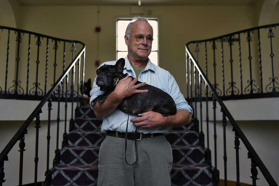 Michael Peterson, a finish carpenter who suffered two strokes that cut short his working life, holds Sara, his French bulldog Sara, at their apartment building in Alameda. Photo: Michael Short, Special To The Chronicle